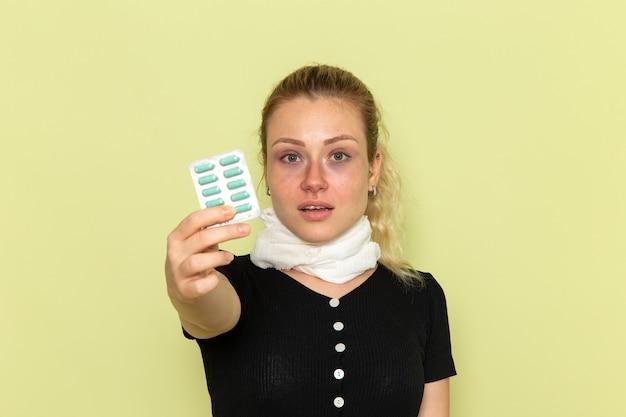 녹색 벽 질병 여성 의학 질병에 매우 아프고 아픈 약을 들고 전면보기 젊은 여성 느낌