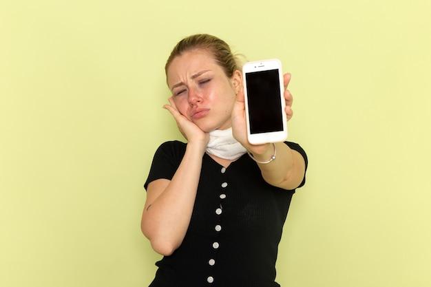 Giovane donna di vista frontale che si sente molto malato e malato che tiene il suo telefono sulla malattia della medicina di malattia della parete verde