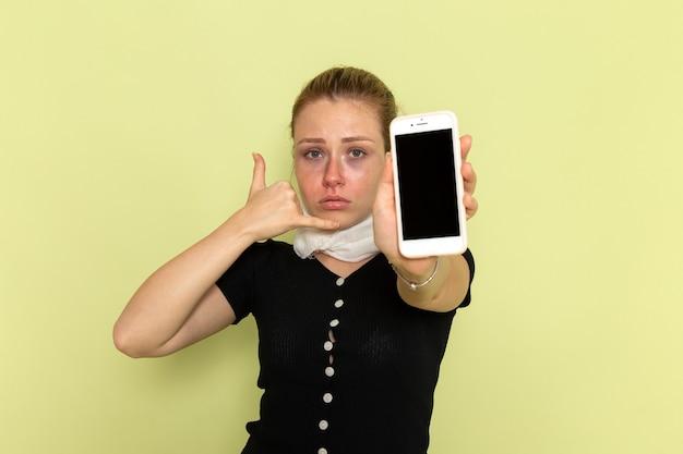 Giovane donna di vista frontale che si sente molto malato e malato che tiene il suo telefono sulla malattia della medicina di malattia della parete verde chiaro