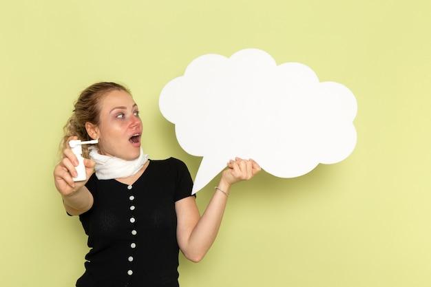 Giovane femmina di vista frontale che si sente molto malato e malato che tiene enorme segno bianco che tiene spray sulla parete verde malattia medicina salute malattia