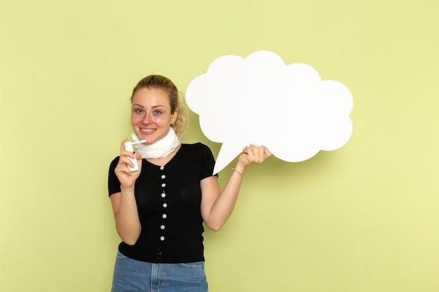 Giovane donna di vista frontale che si sente molto male e malato che tiene enorme segno bianco che tiene spray sorridente sulla parete verde malattia medicina salute malattia
