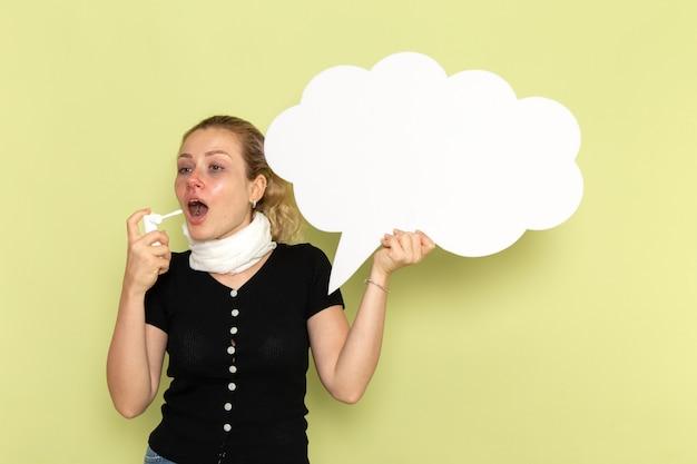 Giovane donna di vista frontale che si sente molto malato e malato che tiene un enorme segno bianco utilizzando spray sulla parete verde malattia medicina salute malattia