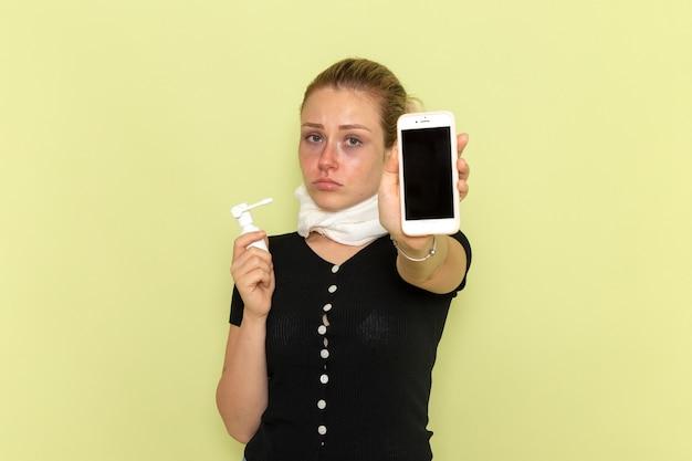 Giovane femmina di vista frontale che si sente molto malato e malato che tiene il telefono e lo spruzzo sulla malattia della medicina di malattia della parete verde