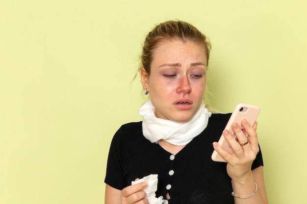 Giovane donna di vista frontale che si sente molto malato e malato parlando al telefono sulla parete verde femminile malattia medicina malattia