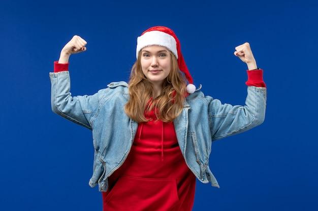 Вид спереди молодая женщина сгибается и улыбается на синем фоне эмоции цвета рождественского праздника