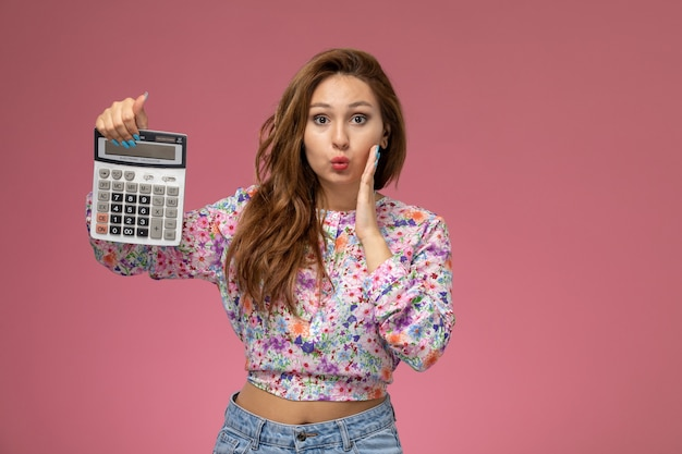 Front view young female in flower designed shirt and blue jeans holding calculator on pink desk