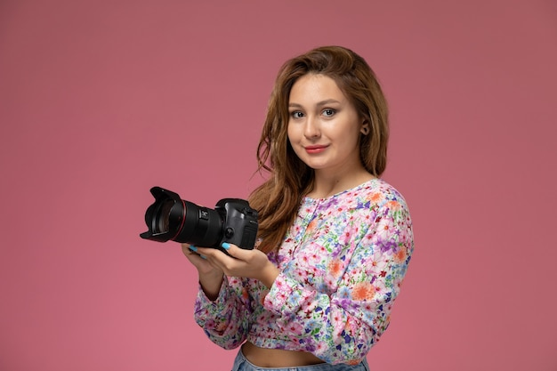 Front view young female in flower designed shirt and blue jeans holding a photo camera on the pink background