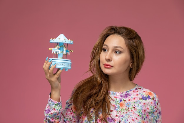 Front view young female in flower designed shirt and blue jeans holding souvenir on the pink background