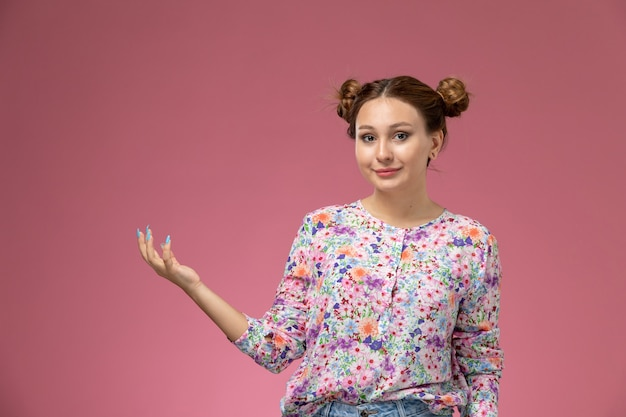 Front view young female in flower designed shirt and blue jeans just posing with smile on pink background