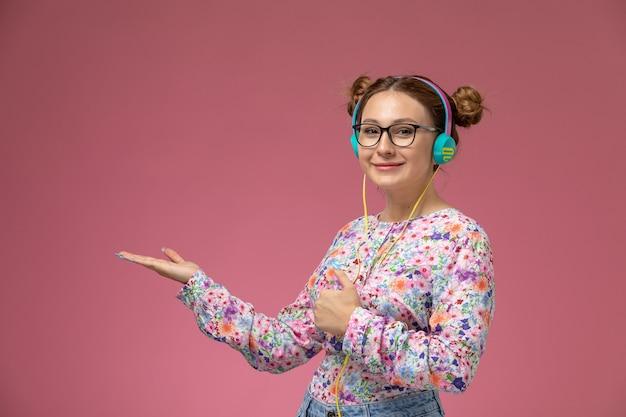 Vista frontale giovane femmina in fiore progettato camicia e blue jeans ascoltando musica con il sorriso sul suo viso su sfondo rosa