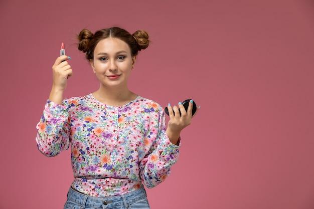 Vista frontale giovane femmina in camicia fiore progettato e blue jeans sorridente azienda lucidalabbra su sfondo rosa