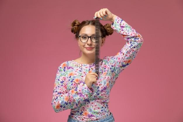 Vista frontale giovane femmina in fiore progettato camicia e blue jeans sorridendo e tenendo il vecchio nastro di film su sfondo rosa