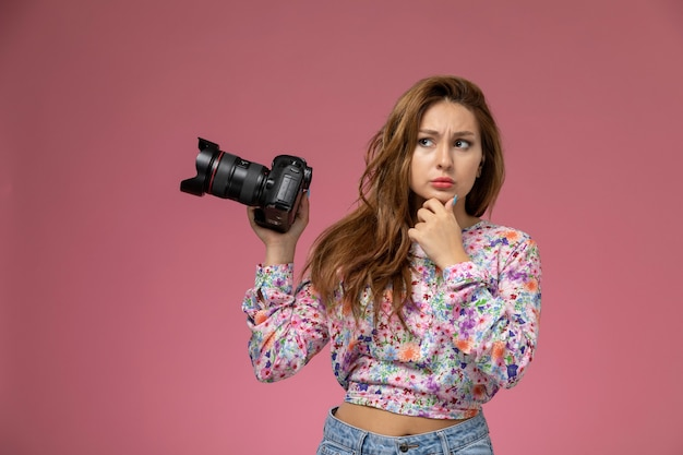 Front view young female in flower designed shirt and blue jeans thinking and holding photo camera on the pink background