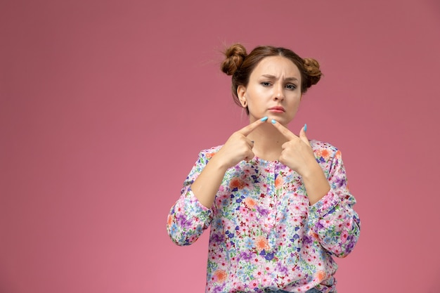 Front view young female in flower designed shirt and blue jeans touching her acne on the pink background
