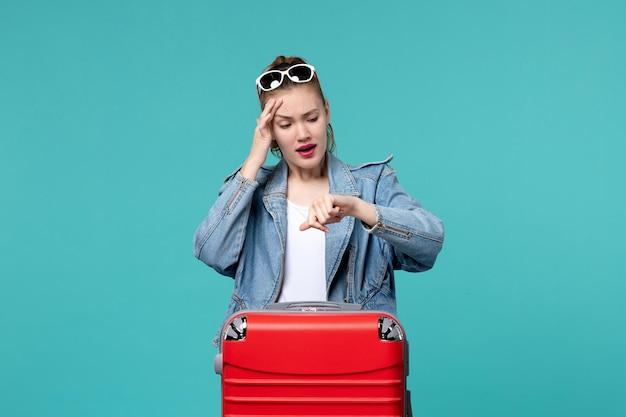 Вид спереди молодая женщина готовится к поездке и проверяет время на синем пространстве
