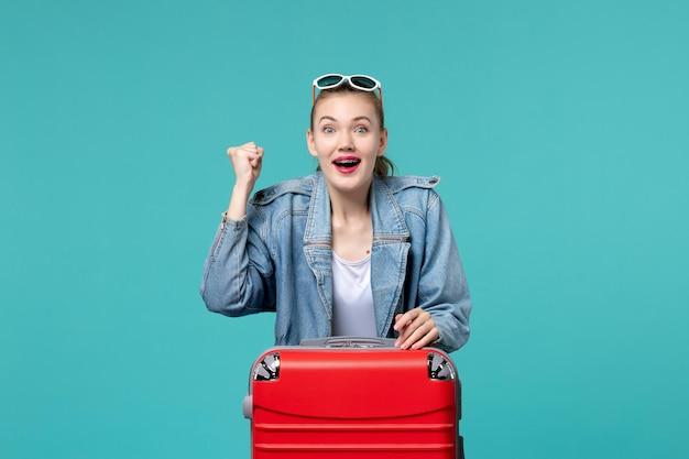 Вид спереди молодая женщина готовится к поездке, чувствуя себя взволнованной на синем пространстве