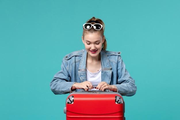 전면보기 젊은 여성 여행을 준비하고 밝은 파란색 공간에 흥분된 느낌