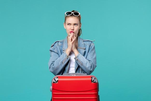 旅行の準備をして青い空間を考えている正面図若い女性