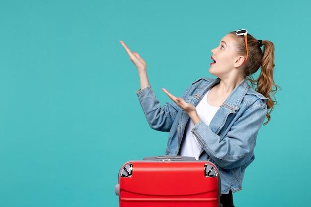 푸른 공간에 여행을 준비하는 전면보기 젊은 여성