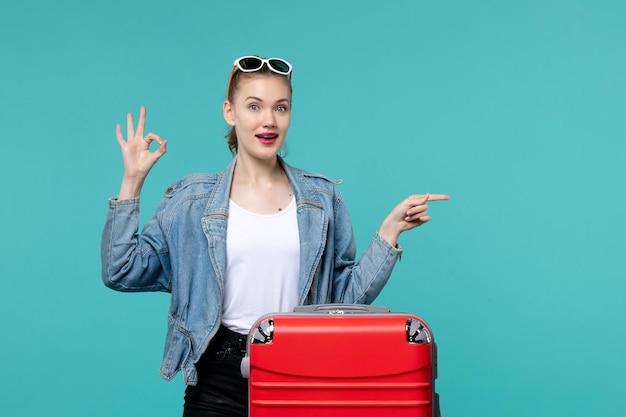 파란색 책상에 여행을 준비하는 전면보기 젊은 여성