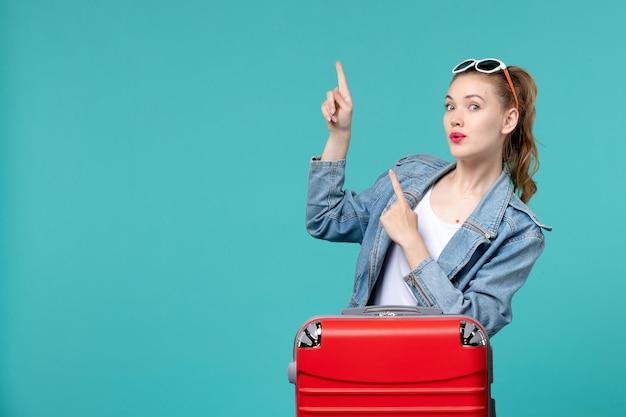 Вид спереди молодая женщина готовится к поездке на синем пространстве