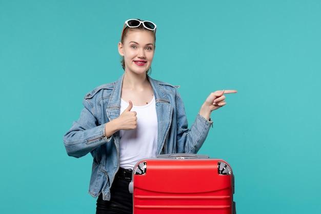 밝은 파란색 공간에 여행을 준비하는 전면보기 젊은 여성