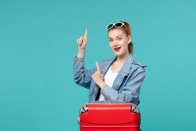 青いスペースで旅行の準備をしている正面図若い女性