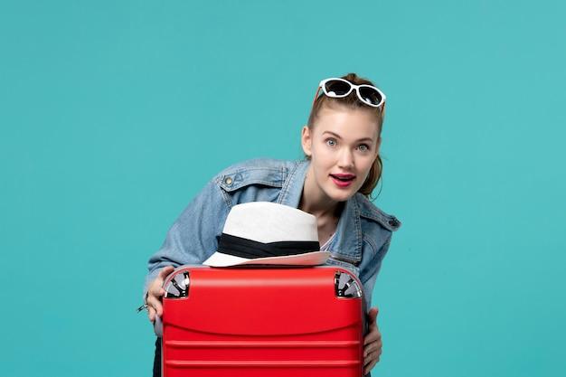 푸른 공간에 그녀의 빨간 가방과 함께 여행을 준비하는 전면보기 젊은 여성