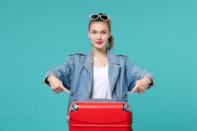 파란색 책상에 그녀의 빨간 가방과 함께 여행을 준비하는 전면보기 젊은 여성