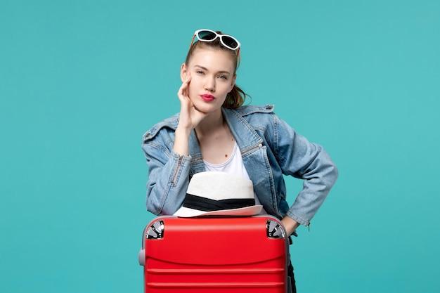 Вид спереди молодая женщина готовится к поездке со своей красной сумкой на синем пространстве