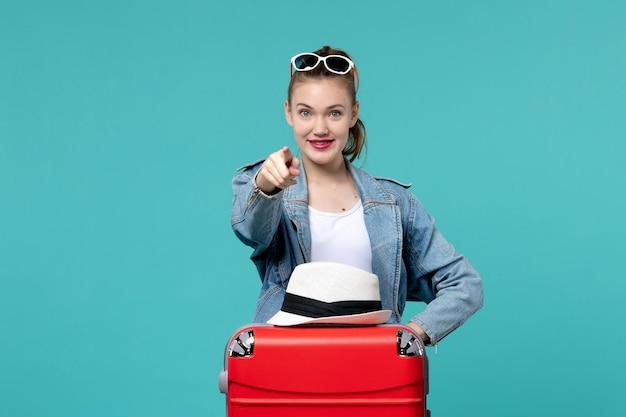 파란색 공간에 빨간 가방과 모자와 함께 여행을 준비하는 전면보기 젊은 여성