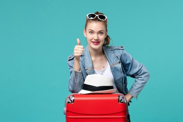 Вид спереди молодая женщина готовится к поездке с красной сумкой и шляпой на синем пространстве