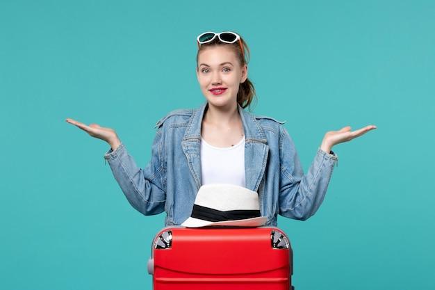 푸른 공간에 빨간 가방 여행을 준비하는 전면보기 젊은 여성