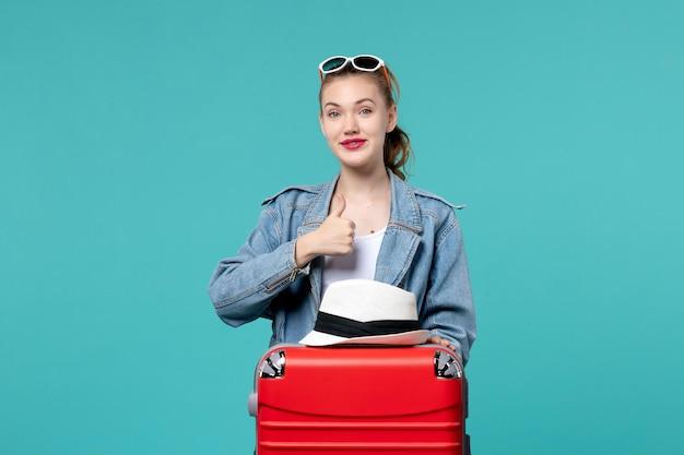 Вид спереди молодая женщина готовится к поездке с красной сумкой на синем пространстве