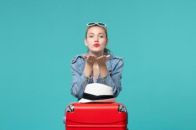 青いスペースに赤いバッグを持って旅行の準備をしている正面図若い女性