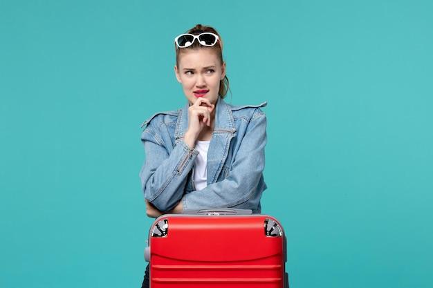 Giovane femmina di vista frontale che si prepara per il viaggio e pensa sullo spazio blu