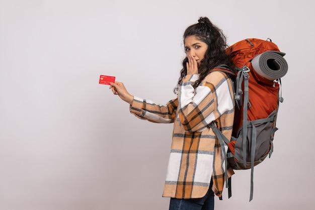 Vista frontale giovane donna che va in escursionismo tenendo la carta di credito su sfondo bianco aria turistica foresta altezza campus montagna natura