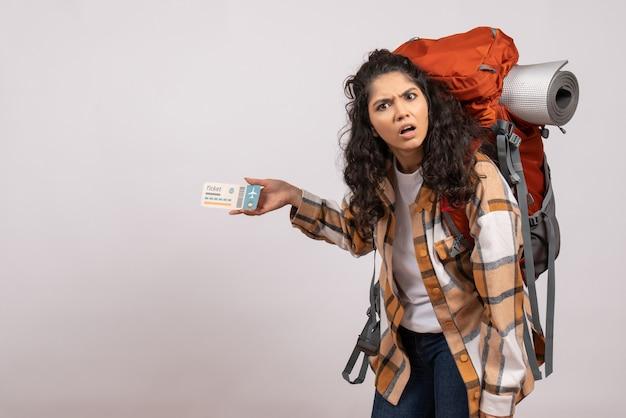 Vista frontale giovane femmina che va in escursionismo tenendo il biglietto su sfondo bianco turista foresta vacanza volo viaggio campus montagna