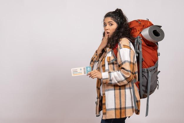 Vista frontale giovane donna che va in escursionismo tenendo il biglietto su sfondo bianco viaggio aereo turistico foresta vacanza volo campus