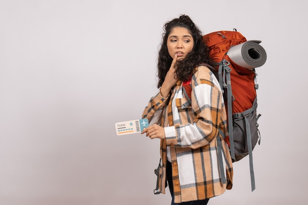 Front view young female going in hiking holding ticket on the white background trip tourist vacation flight campus air mountain forest