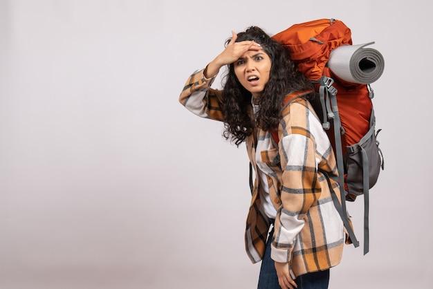 Vista frontale giovane donna che va in escursionismo con zaino su sfondo bianco vacanza campus montagna viaggio foresta aria turistica