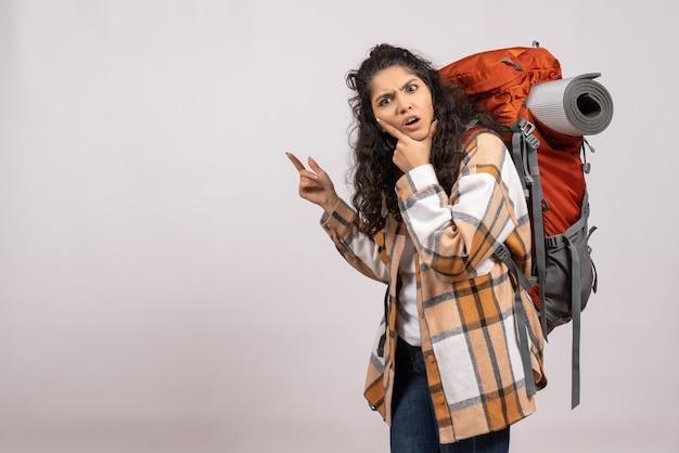Vista frontale giovane donna che va in escursionismo con lo zaino su uno sfondo bianco viaggio nella foresta vacanza aria di montagna campus turistico