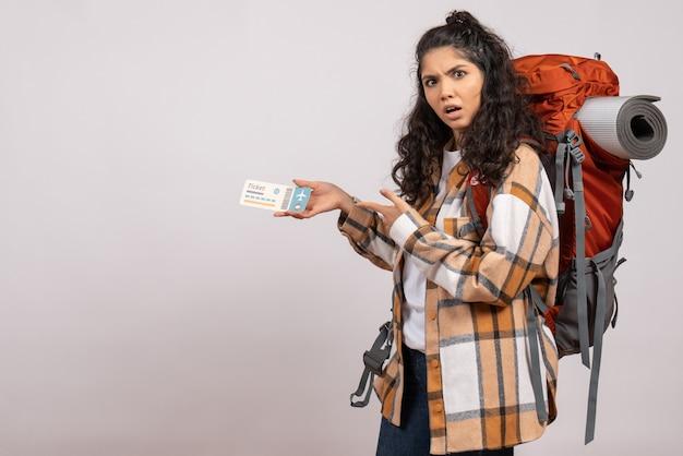 白い背景の空気の森の休暇の飛行旅行のキャンパスの山にチケットを持ってハイキングに行く正面の若い女性