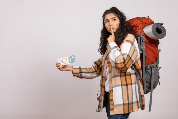 Вид спереди молодая женщина, идущая в походы с билетом на белом фоне, поездка, воздушный туристический лес, каникулы, кампус, гора