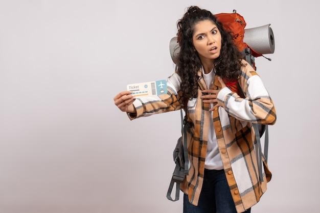 Вид спереди молодая женщина, идущая в походы с билетом на белом фоне, поездка, воздушный турист, лес, отпуск, полет, кампус, гора