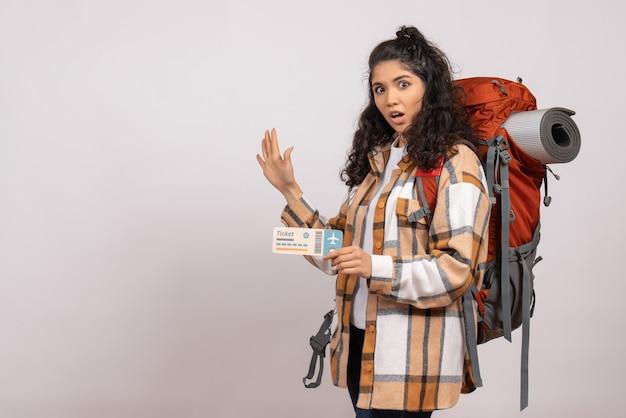 Вид спереди молодая женщина, идущая в походы с билетом на белом фоне, поездка, туристический отпуск, рейс, воздушный горный лес