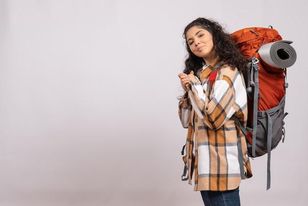 白い背景のキャンパス観光休暇山の森の空気にバックパックを持ってハイキングに行く正面の若い女性