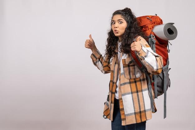 白い背景のキャンパス休暇の山の森の空気観光客にバックパックを持ってハイキングに行く正面の若い女性
