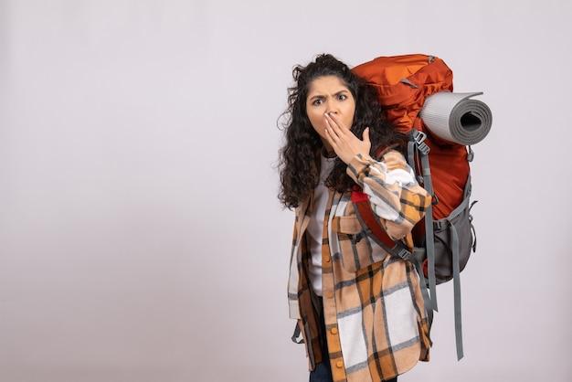白い背景の森旅行休暇山観光キャンパスにバックパックを持ってハイキングに行く正面の若い女性