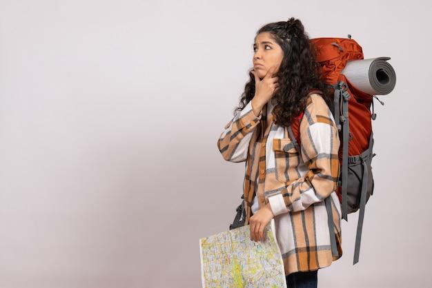 白い背景の高さのキャンパスの森の山の観光の空気自然に地図を持ってハイキングに行く正面の若い女性